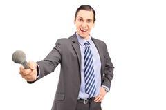 Um repórter masculino profissional que guardara um microfone Fotos de Stock Royalty Free