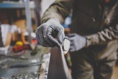 Um reparador do homem no serviço do esqui da oficina que repara a superfície de deslizamento do esqui no torno do esqui Nas mãos  imagem de stock