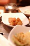 Um restaurante coreano tradicional com os vários pratos laterais Pratos laterais da refeição coreana do sprou vegetal do feijão d Fotografia de Stock