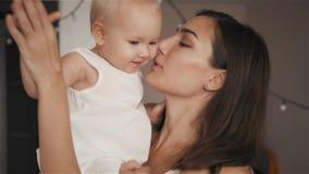 Um retrato da mãe nova feliz com um bebê em casa que beija e que ri vídeos de arquivo