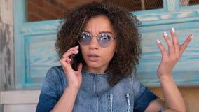 Um retrato da mulher afro-americana que fala pelo telefone com a cara infeliz imagem de stock