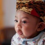 Um retrato de um beb? 3 m?s-velho que mostra um Blangkon do sorriso e vestir Blangkon ? uma coberta principal t?pica da ilha de J imagens de stock royalty free