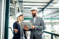 Um retrato de um coordenador industrial do homem e da mulher com tabuleta em uma fábrica, trabalhando fotos de stock
