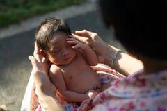 Um retrato de um menino 42 dias de idade carregado em um nascimento dos lótus com sua mãe Ao contrário dos bebês geralmente, o ca foto de stock