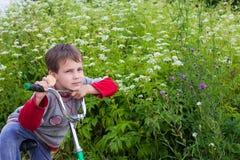 Um retrato de um menino que monta uma bicicleta no país imagem de stock