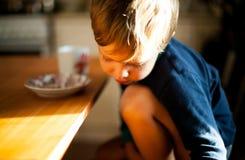 Um retrato de um menino que senta apenas a vista para baixo imagem de stock