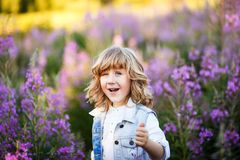 Um retrato de um rapaz pequeno bonito com olhos azuis e cabelo louro longo fora no campo das flores que têm o divertimento imagem de stock royalty free