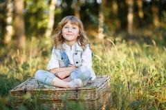 Um retrato de um rapaz pequeno bonito com os olhos azuis e o cabelo louro longo que sentam-se em uma cesta fora no por do sol imagens de stock royalty free