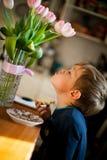 Um retrato de um rapaz pequeno que come o café da manhã em casa fotografia de stock