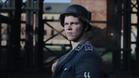 Um retrato de um soldado novo em um uniforme alemão que olha a sua cabeça esquerda, girando, e olhando em linha reta Ww2 filme
