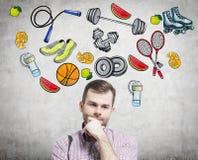 Um retrato de um homem considerável de sonho que esteja pensando sobre sua escolha da atividade do esporte Os ícones coloridos do Fotografia de Stock Royalty Free