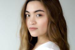 Um retrato de uma jovem mulher que veste uma camisa branca imagem de stock