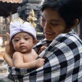 Um retrato de uma m?e com seu beb? que tem 3 meses velho nos bra?os da m?e Os beb?s levantam usando faixas t?picas do Balinese e foto de stock