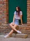 Um retrato de uma menina bonita com cabelo escuro na roupa ocasional que levanta em um fundo verde da porta Conceito urbano na mo fotografia de stock royalty free