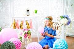 Um retrato de uma menina bonita em um estúdio decorou muitos balões da cor Imagens de Stock