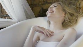 Um retrato de uma menina loura bonita na parte superior sem alças branca que senta-se no banho vazio e que ri na parede de tijolo filme