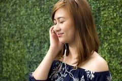 Um retrato de uma mulher bonita está escutando a música imagens de stock