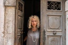 Um retrato de uma mulher loura nova em um vestido cinzento neutro, estando em uma entrada de uma porta gasto imagens de stock