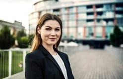 Um retrato de uma mulher de negócios nova que está fora na frente de uma construção imagens de stock