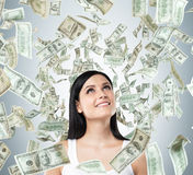 Um retrato de uma senhora sonhadora em uma camiseta de alças branca As notas do dólar estão caindo do teto Imagem de Stock Royalty Free