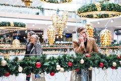 Um retrato do adolescente com o smartphone no shopping no Natal fotografia de stock