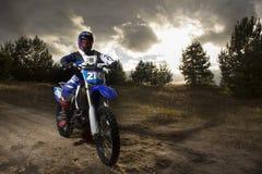 Um retrato do cavaleiro do motocross que sitiing na bicicleta no fundo do por do sol Imagens de Stock