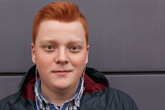 Um retrato do close-up do menino freckled do ruivo atrativo com a cara redonda que tem o corte de cabelo à moda que veste a roupa Imagens de Stock