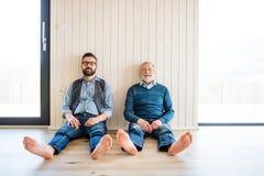 Um retrato do filho adulto do moderno e do pai superior que sentam-se no assoalho dentro em casa foto de stock