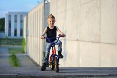 Um retrato do menino considerável com bicicleta fora foto de stock royalty free