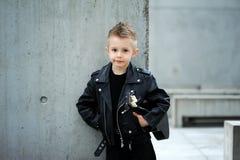 Um retrato do menino considerável, sensível no casaco de cabedal e do corte de cabelo iroquois imagem de stock