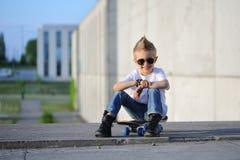 Um retrato do menino desafiante com skate fora fotos de stock