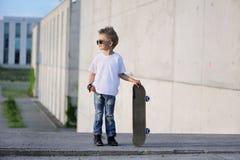 Um retrato do menino desafiante com skate fora fotografia de stock royalty free