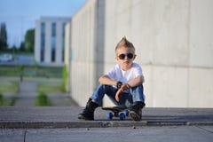 Um retrato do menino desafiante com skate fora imagens de stock