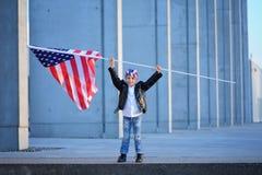 Um retrato do menino feliz que guarda a bandeira americana imagens de stock