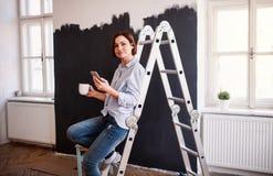 Um retrato do preto da parede da pintura da jovem mulher Uma partida da empresa de pequeno porte fotos de stock royalty free