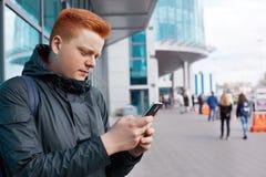 Um retrato lateral do homem novo com o cabelo vermelho que veste o revestimento à moda que guarda o smartphone que está contra o  Imagem de Stock