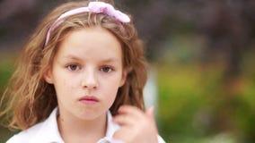 Um retrato próximo de uma menina séria, incomodada Tem uma cara triste, dificuldades na educação, adolescência filme