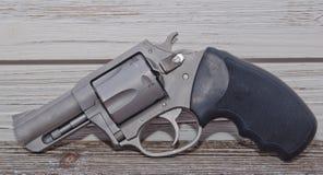 Um revólver em um fundo de madeira Fotografia de Stock