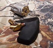 Um revólver em um fundo do camo Fotos de Stock