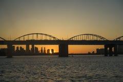 Um rio calmo e uma ponte e um por do sol do arco no parque de Hangang, Seoul, Coreia do Sul imagem de stock