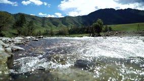 Um rio flui sobre rochas em montanhas bonitas do th vídeos de arquivo