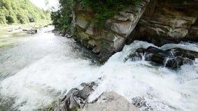 Um rio flui sobre rochas nesta cena bonita nas montanhas Movimento lento filme