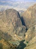 Um rio funciona através de uma garganta enorme em Afeganistão foto de stock