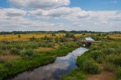 Um rio pequeno que corre com os campos e a reflexão das nuvens na água Foto de Stock