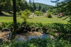 Um rio pequeno que flui perto do complexo do hotel com um campo de jogos do ` s das crianças e uma grande área do parque Foto de Stock Royalty Free