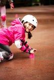 Um rolo caucasiano pequeno do novato da menina que cai na terra no parque do outono no dia chuvoso imagem de stock