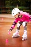 Um rolo caucasiano pequeno do novato da menina que cai na terra no parque do outono no dia chuvoso foto de stock