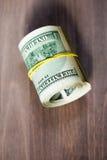 Um rolo de cem notas de dólar dos E.U. Imagem de Stock