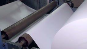 Um rolo de papel largo é girado na máquina para uns cortes mais adicionais 4 video estoque