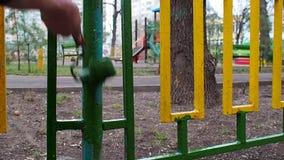 Um rolo do verde da pintura do trabalhador que pinta uma cerca verde-amarela no campo de jogos do fundo video estoque